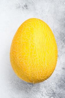 Melão maduro amarelo inteiro. fundo branco. vista do topo.