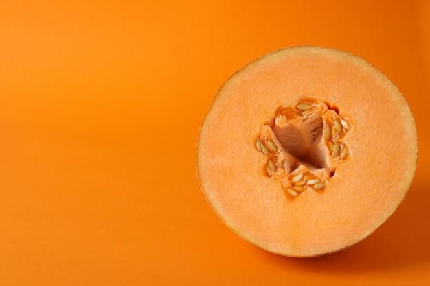 Melão maduro em fundo laranja, espaço para texto