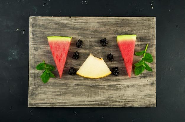 Melão, melancia, amoras e hortelã em uma mesa de madeira