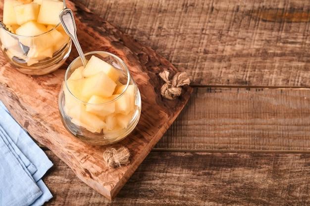 Melão. pedaços de melão fresco para fazer sobremesa de frutas em vidro em um fundo de madeira velho. brincar. vista do topo.