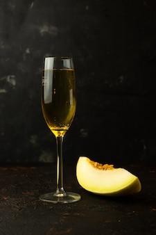 Melão pequeno amarelo suculento com uma taça de champanhe em cima da mesa