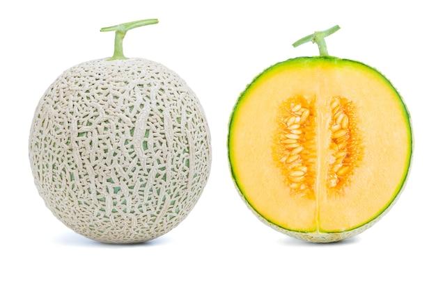 Melão verde doce fresco inteiro e cortado ao meio isolado sobre fundo branco