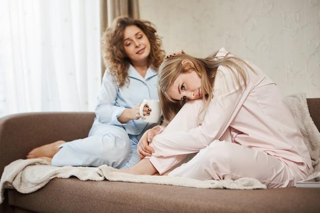 Melhor amiga animar loira de coração partido. retrato de duas mulheres atraentes, sentado no sofá em roupas de noite. menina de cabelos encaracolados tomando café, dando tapinhas na cabeça da irmã enquanto ela está chateada ou sentindo cólicas