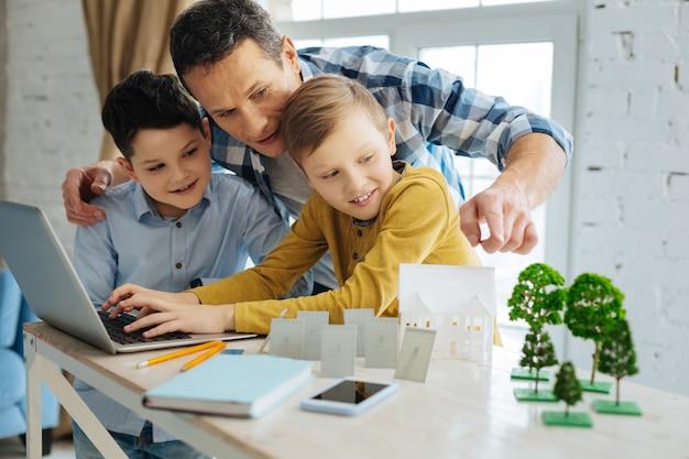 Melhor assistente. jovem pai amoroso dando conselhos aos filhos sobre o projeto ecológico deles enquanto os meninos buscam novas informações no laptop