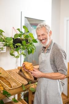 Melhor cozimento. delicioso homem barbudo de cabelos grisalhos com croissant nas mãos perto de uma prateleira com doces em uma mini padaria