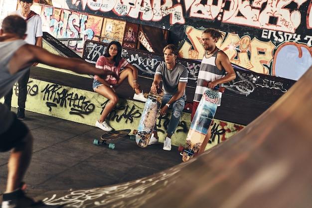 Melhor dia para andar de skate. grupo de jovens modernos saindo juntos enquanto passam o tempo na pista de skate ao ar livre