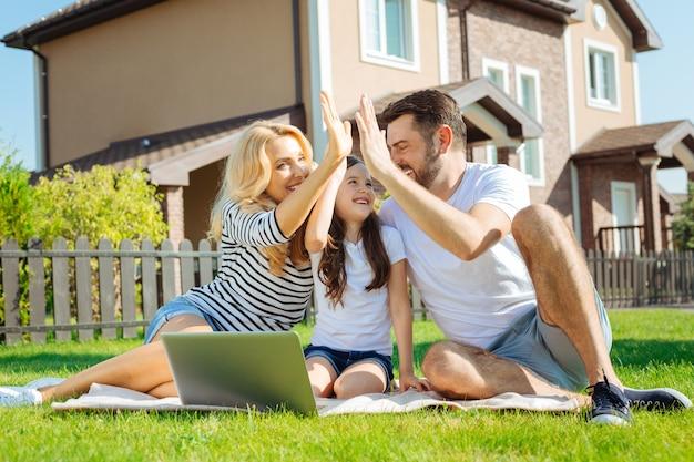 Melhor equipe. adorável jovem família sentada na grama em seu quintal e dando-se cumprimentando
