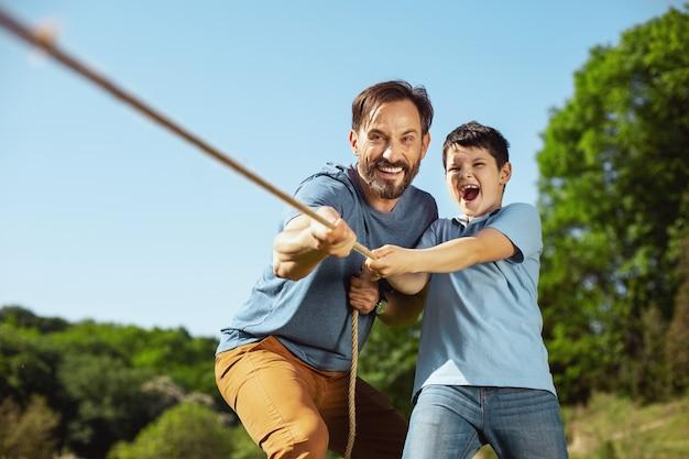 Melhor equipe. pai amoroso inspirado ajudando seu filho enquanto puxava uma corda com sua irmã