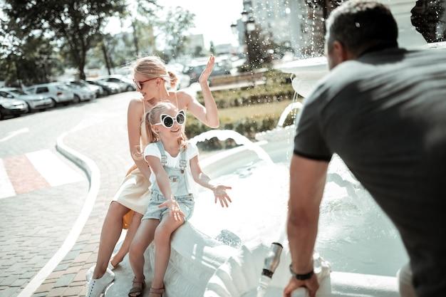 Melhor família. alegre menina brincando com seus pais perto de uma bela fonte branca na cidade.