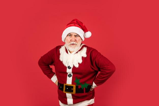 Melhor feriado. feliz natal. barbudo santa no chapéu sobre fundo vermelho. presentes de natal e hora de compras de presentes. alegria do feriado de inverno. homem sério sênior com fantasia de papai noel. feliz ano novo de 2021.