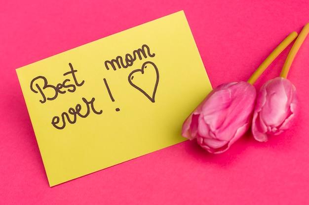 Melhor mãe já título em papel amarelo perto de tulipas brilhantes