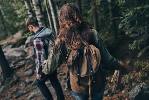 Melhor maneira de escapar da cidade. vista traseira de um jovem casal caminhando juntos na floresta enquanto aproveita a viagem Foto Premium