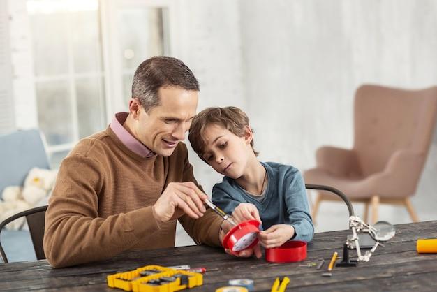 Melhor pai. homem bonito e alegre de cabelos escuros mostrando instrumentos para o filho enquanto está sentado na mesa e o ensinando