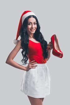 Melhor presente de natal para meninas! mulher jovem e atraente com chapéu de papai noel segurando um sapato de salto alto e sorrindo em frente a um fundo cinza
