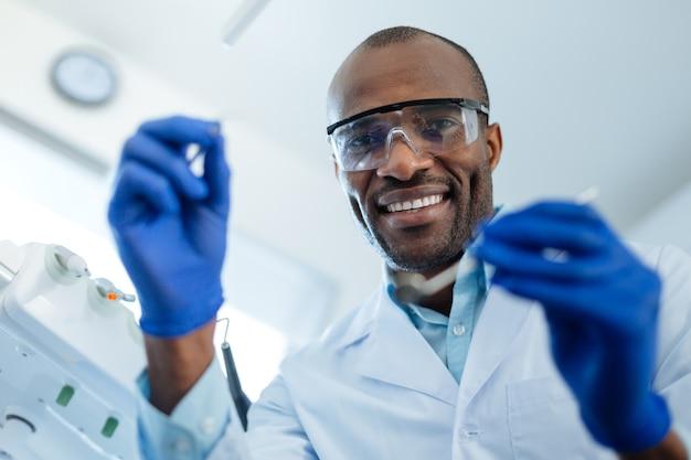 Melhor profissional. alegre e agradável dentista masculino segurando um espelho bucal e uma sonda dentária e sorrindo para a câmera, sendo preparado para um exame de cárie