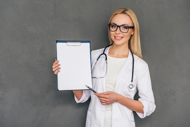 Melhor receita para você! bela jovem médica apontando para sua prancheta e olhando para a câmera com um sorriso em pé contra um fundo cinza