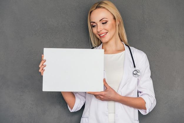 Melhor receita para você! bela jovem médica segurando o espaço da cópia e olhando para ele com um sorriso em pé contra um fundo cinza