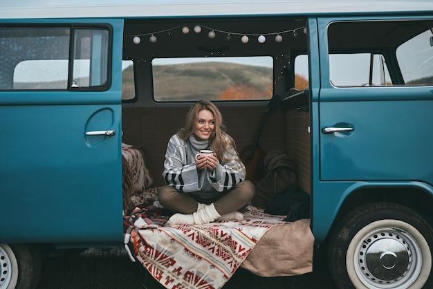 Melhor viagem de todas. mulher jovem e atraente sorridente segurando uma caneca e desviando o olhar enquanto está sentado dentro da mini van azul estilo retro