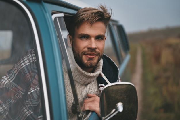 Melhor viagem. jovem bonito inclinando-se para fora da janela da van e sorrindo enquanto está sentado no banco do passageiro da frente Foto Premium