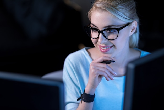 Melhorando minhas habilidades. sorridente, charmoso programador confiante sentado no escritório e usando computadores enquanto trabalha para resolver códigos de senha