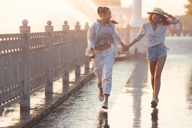 Melhores amigas a passear ao lado de uma fonte