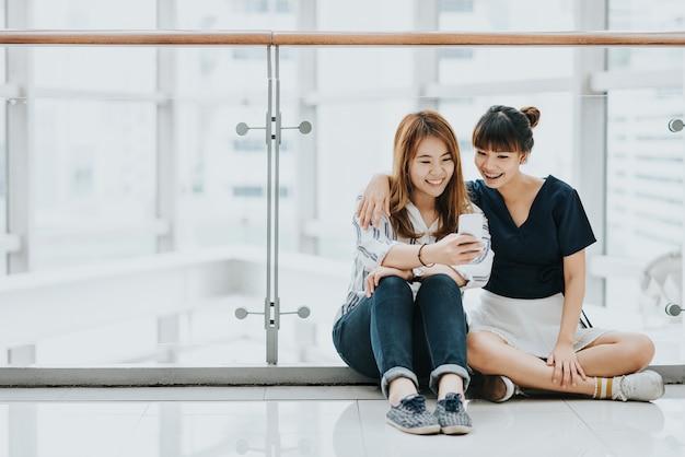 Melhores amigas asiáticas felizes riem e se divertem com o smartphone