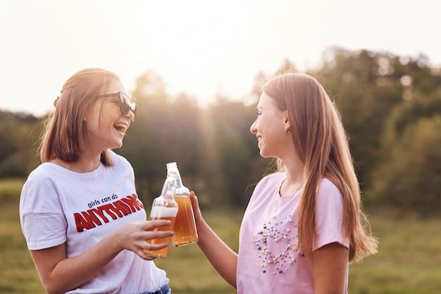 Melhores amigas brindam com garrafas de cerveja gelada, se divertem juntas, passam o tempo livre ao ar livre