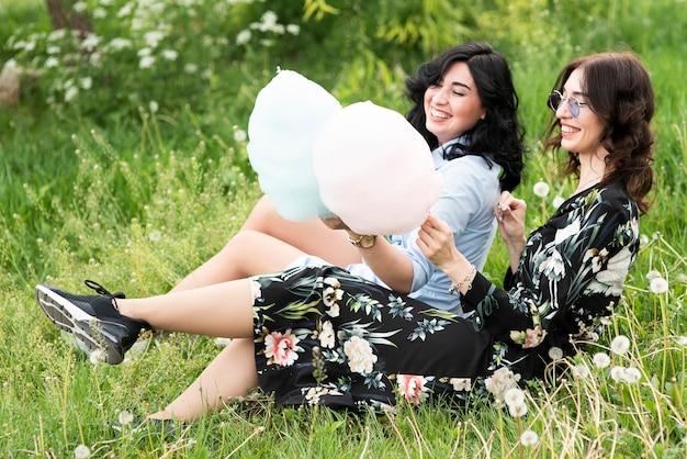 Melhores amigas com algodão doce, permanecendo na grama