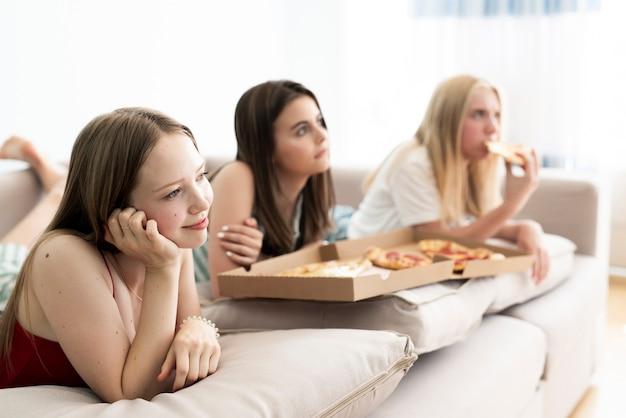 Melhores amigas comendo pizza em casa
