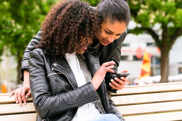 Melhores amigas conversando com smartphone no banco do parque