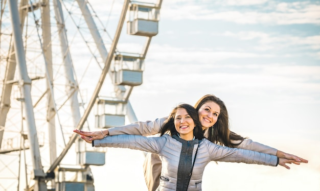 Melhores amigas de mulheres jovens, aproveitando o tempo juntos ao ar livre na roda gigante