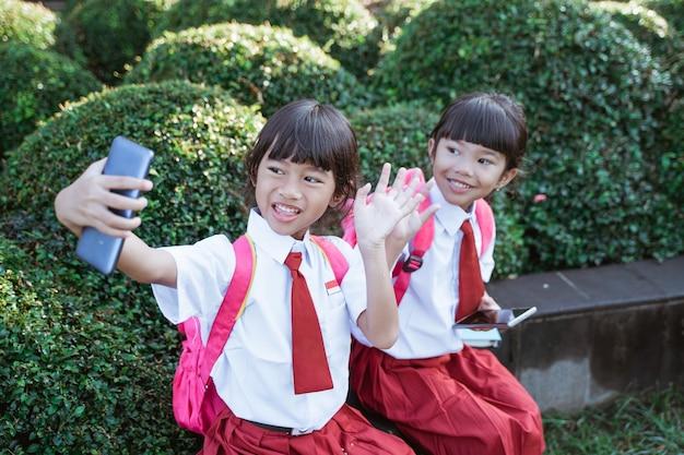 Melhores amigas de uma estudante do ensino fundamental da indonésia tirando uma selfie