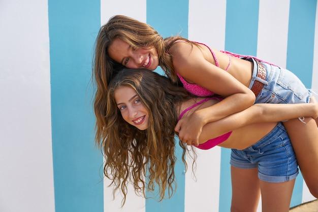 Melhores amigas meninas nas costas na praia de verão