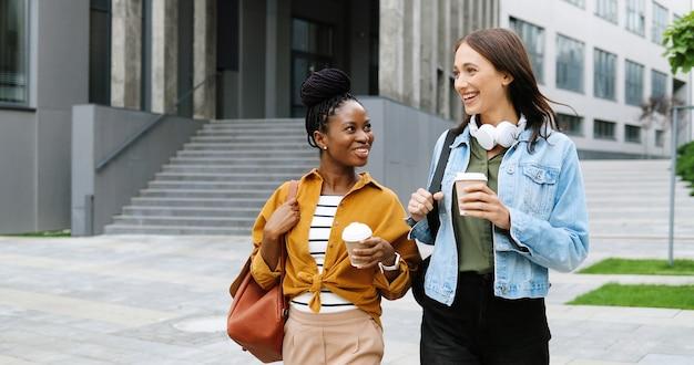 Melhores amigas mestiças, jovens e lindas amigas conversando animadamente e caminhando com xícaras de café para viagem e nas ruas da cidade. estudantes multiétnicas elegantes e felizes passeando ao ar livre com bebidas quentes