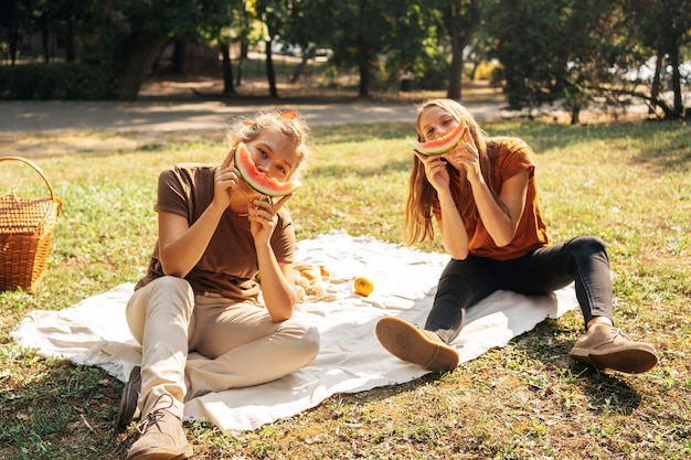Melhores amigas posando enquanto comem melancia