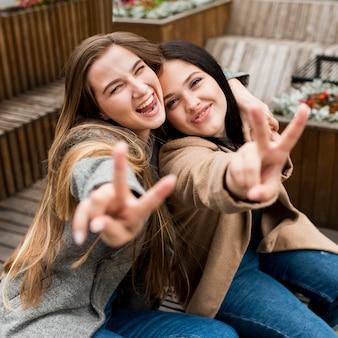 Melhores amigas posando enquanto mostram o símbolo da paz