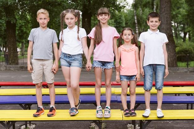 Melhores amigas, posando no banco colorido