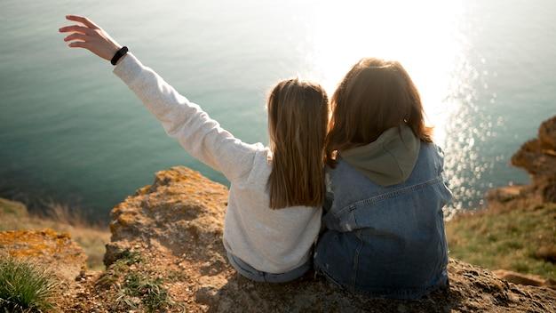 Melhores amigas se abraçando e oceano