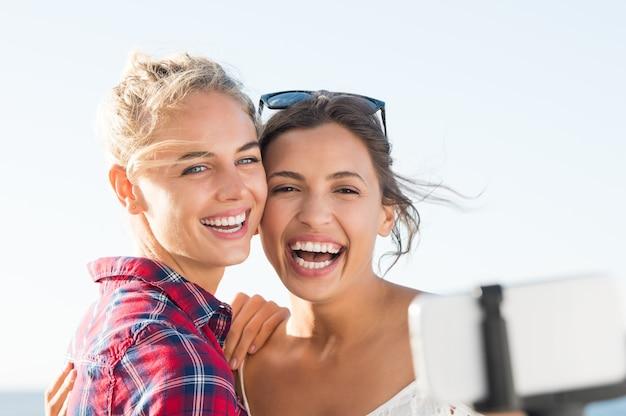Melhores amigas se divertindo tirando selfie ao ar livre