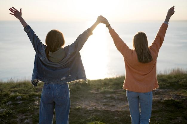 Melhores amigas, segurando suas mãos no ar