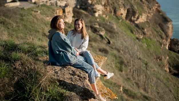 Melhores amigas sentadas em uma colina