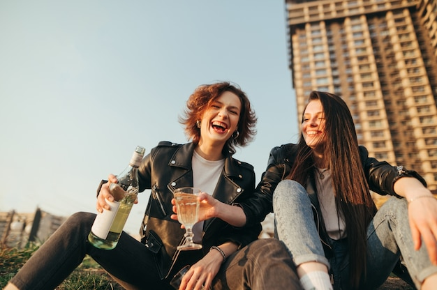Melhores amigas sorridentes bebem vinho em uma caminhada