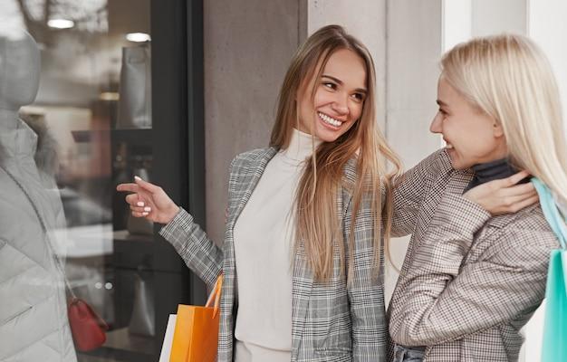 Melhores amigas sorridentes em roupas elegantes e com sacolas de papel perto da vitrine e olhando umas para as outras durante as compras