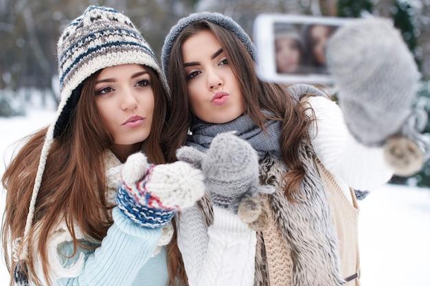 Melhores amigas tirando selfie no inverno
