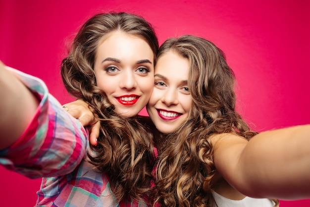 Melhores amigas tomando selfie com a câmera.