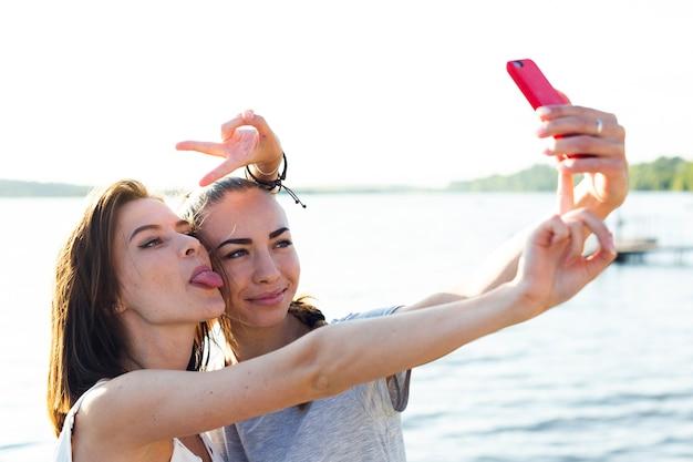 Melhores amigas tomando um selfie ao lado de um lago