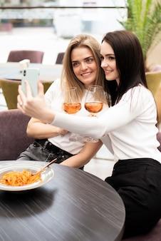 Melhores amigas tomando uma selfie com seus copos de vinho
