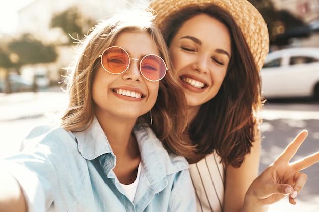 Melhores amigas vestindo roupas elegantes e tirando selfie na rua