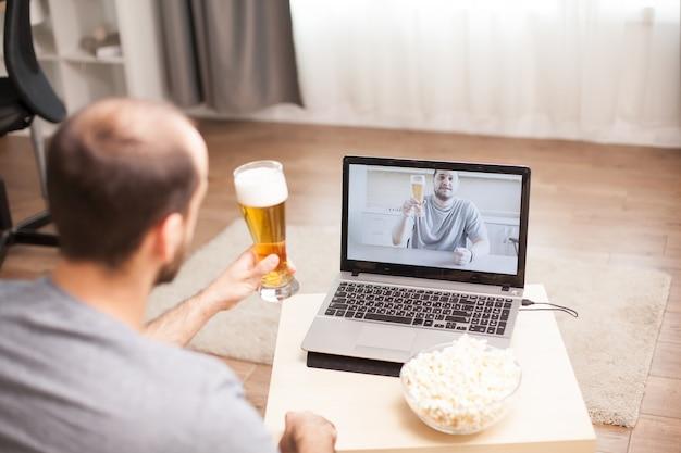 Melhores amigos bebendo cerveja em uma videochamada durante a quarentena.