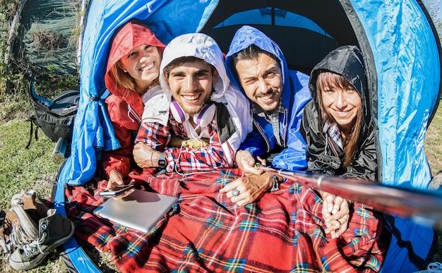 Melhores amigos casais tirando selfie em uma barraca de acampamento em um dia ensolarado após a chuva